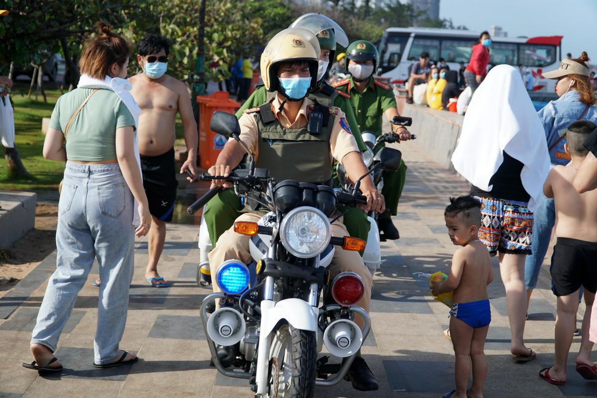 Cảnh sát tuần tra liên tục trên bờ kè biển Bãi Sau để nhắc nhở người dân đeo khẩu trang, không được xuống biển. Ảnh: Trường Hà.