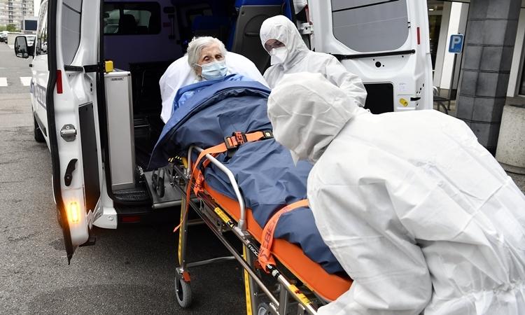 Nhân viên y tế di chuyển cụ bà 100 tuổi đã chiến thắng nCoV ở Bỉ ngày 29/4. Ảnh: Reuters.