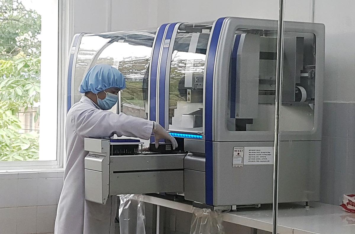 Nhân viên y tế Trung tâm Kiểm soát bệnh tật Quảng Nam làm xét nghiệm mẫu bệnh phẩm. Ảnh: Lệ Diễm.