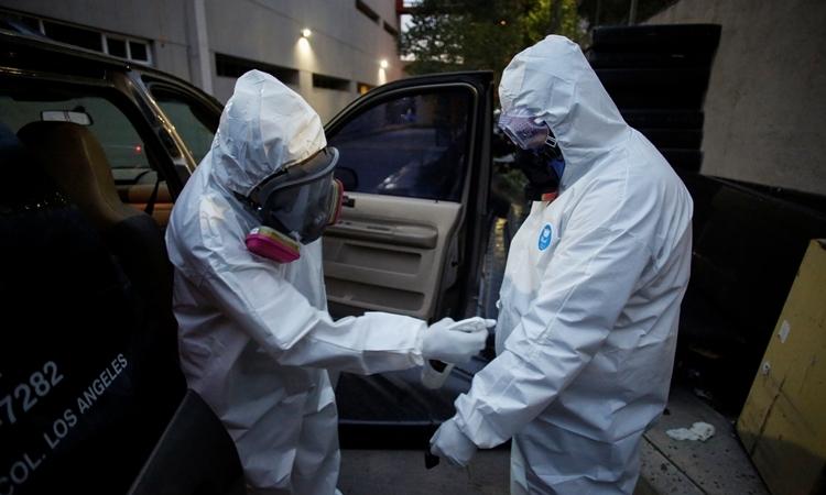 Nhân viên nhà tang lễ khử trùng cho nhau tạiMexico ngày 30/4. Ảnh: Reuters.