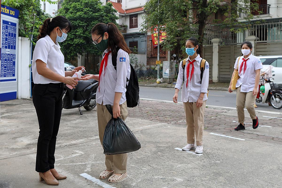 Sáng 4/5, học sinh trường THCS Nguyễn Du, quận Nam Từ Liêm, Hà Nội đứng giãn cách, xếp hàng đo thân nhiệt trước khi vào trường. Ảnh: Ngọc Thành.