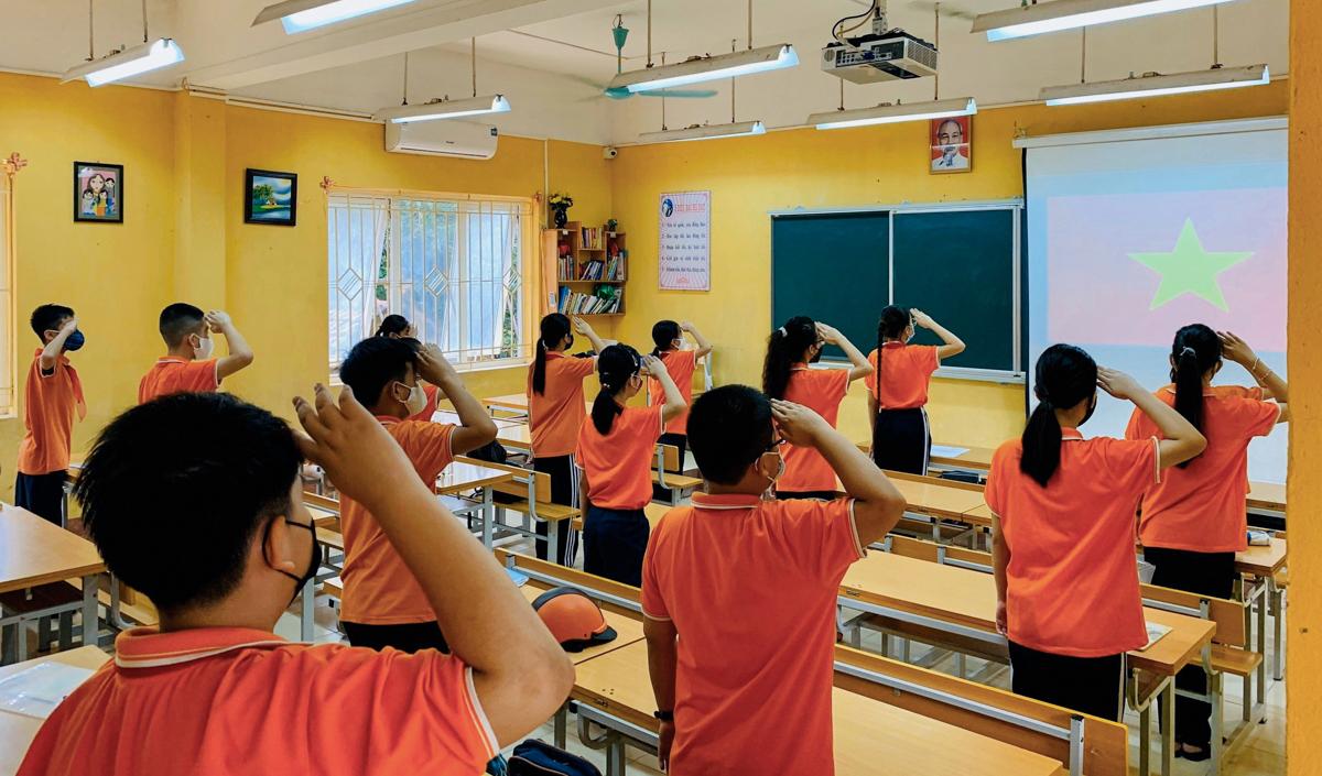 Học sinh trường THCS Nguyễn Trãi, Hà Nội chào cờ tại lớp học trong ngày đầu tiên đi học trở lại. Ảnh: Trường Nguyễn Trãi.