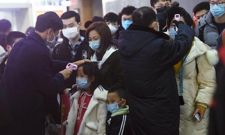 Giới chức y tế ở Hàng Châu đo thân nhiệt hành khách đến từ Vũ Hán ngày 23/1. Ảnh: Reuters.