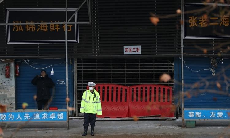 Cảnh sát đừng gác trước cổng chợ Hoa Nam, bị nghi là nơi khởi phát nCoV, thành phố Vũ Hán, Trung Quốc, tháng 2. Ảnh: AFP.
