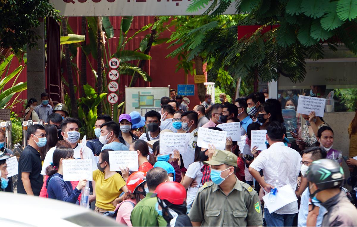 Phụ huynh đứng trước trường Quốc tế Việt Úc (đường 3/2, quận 10, TP HCM) phản đối chính sách thu học phí, sáng 5/5. Ảnh: Mạnh Tùng.