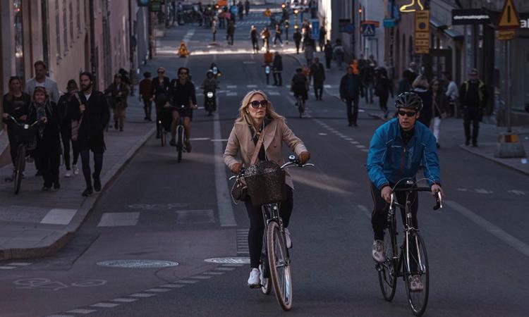 Người dân Thụy Điển đạp xe trên phốGotgatan, thủ đô Stockholm, hồi tháng 4. Ảnh: NYTimes.