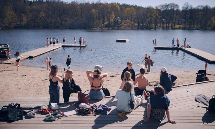 Người dân tập trung tắm nắng trên bãi biểnSickla ởNacka, ngoại ô Stockholm, hồi tháng 4. Ảnh: NYTimes.