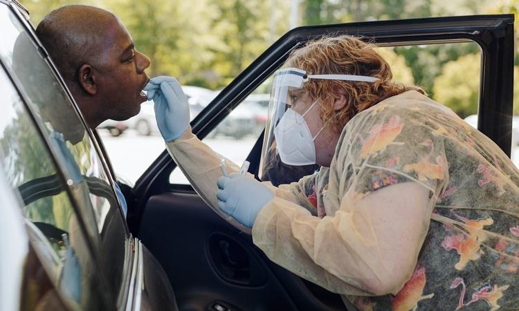 Nhân viên tại phòng khám gia đình Autumn Road ở Arkansas lấu mẫu xét nghiệm cho một bệnh nhân ngay trên xe. Ảnh: NYTimes.