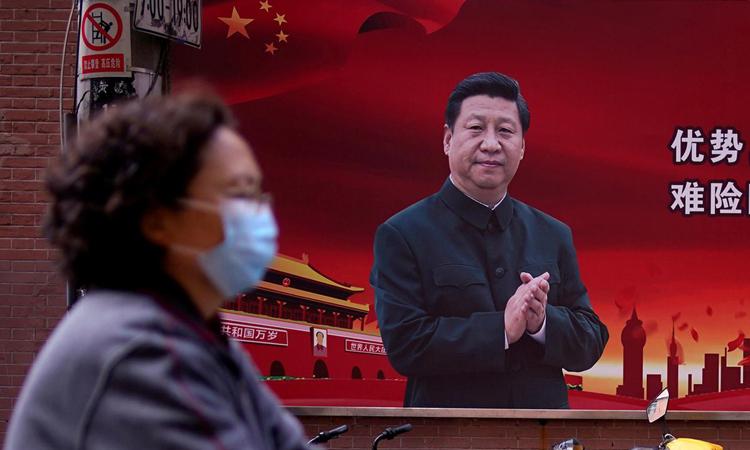 Người phụ nữ đeo khẩu trang đi qua bức ảnh chân dung Chủ tịch Tập Cận Bình trên phố Thượng Hải, Trung Quốc, ngày 12/3. Ảnh:Reuters.