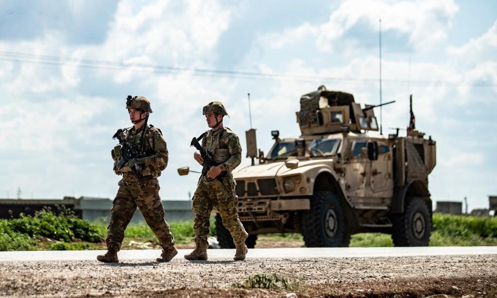 Binh sĩ Mỹ rời thiết giáp kháng mìn chống phục kích (MRAP) để tuần tra trên đường gần làng Tannuriyah, phía đông thành phố Qamishli, Syria, ngày 2/5. Ảnh: AFP.