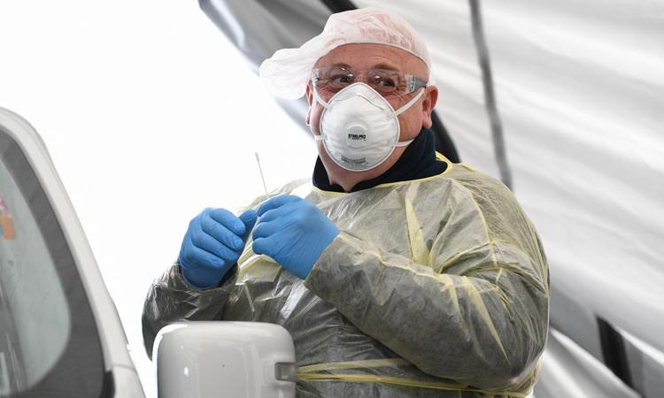 Nhân viên y tế lấy mẫu tại một trạm xét nghiệm nCoV lưu động tại Munich, Đức hôm 11/3. Ảnh: Reuters.