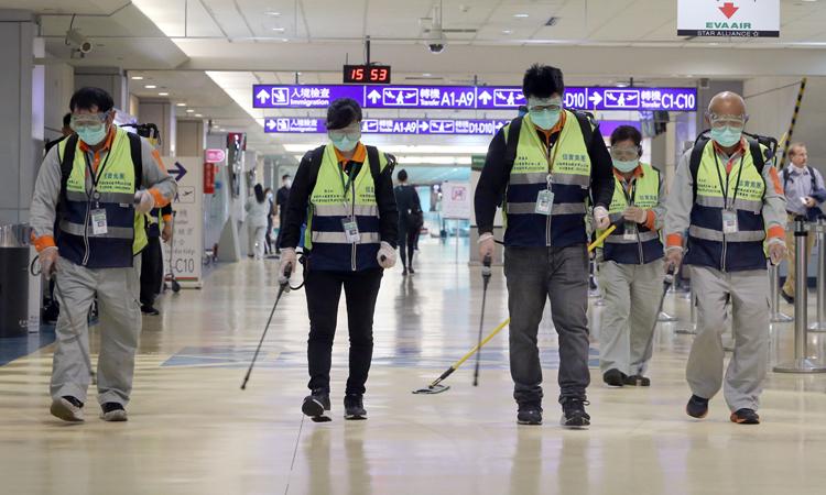Nhân viên phun khử trùng ở sân bay quốc tếTaoyuan, Đài Loan, hôm 22/1. Ảnh: AFP.