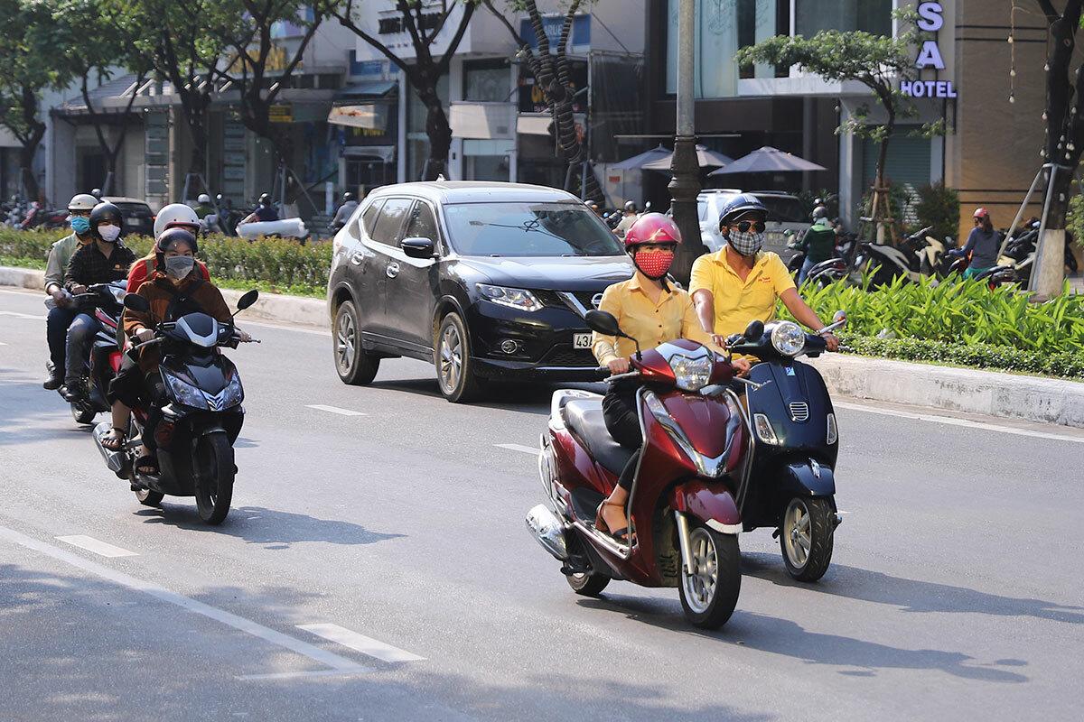 Người dân đi trên đường Nguyễn Văn Linh bị ánh sáng từ toà nhà hắt vào. Ảnh: Nguyễn Đông.
