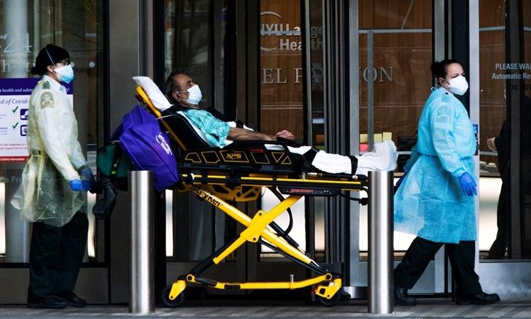 Nhân viên y tế di chuyển bệnh nhân đeo khẩu trang bên ngoài bệnh viện NYU Langone trong đại dịch Covid-19 ở thành phố New York, Mỹ hôm 3/5. Ảnh: Reuters.