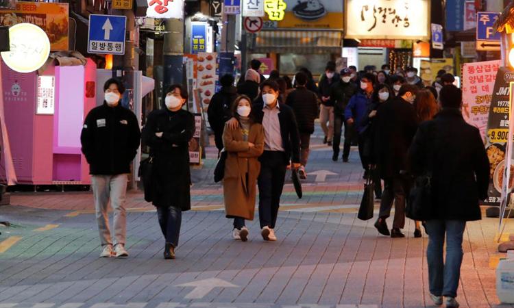 Người dân đeo khẩu trang nhằm phòng chống Covid-19 trên một con phố ở trung tâm Seoul, Hàn Quốc hôm 22/4. Ảnh: Reuters.