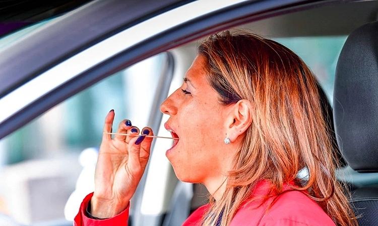 Một phụ nữ tự lấy mẫu dịch họng để xét nghiệm nCoV tại một trạm kiểm tra lái xe ở Alvsjo, Stockholm, Thụy Điển. Ảnh: TT News Agency.