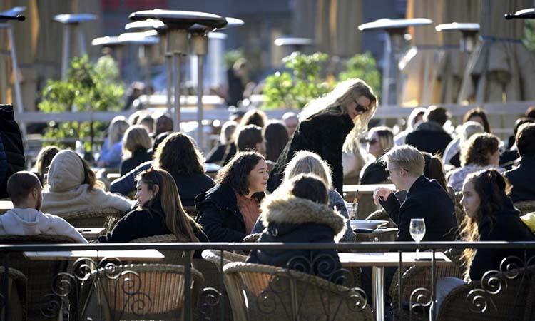 Người dân tận hưởng thời tiết tại một nhà hàng ngoài trời ở Stockholm, Thụy Điển, hôm 26/3, bất chấp Covid-19. Ảnh: Reuters.