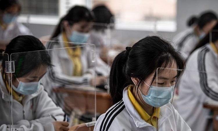 Học sinh đeo khẩu trang và được ngăn cách nhau bằng các tấm nhựa tại một trường trung học ở Vũ Hán, tỉnh Hồ Bắc, Trung Quốc hôm 6/5. Ảnh: AFP.