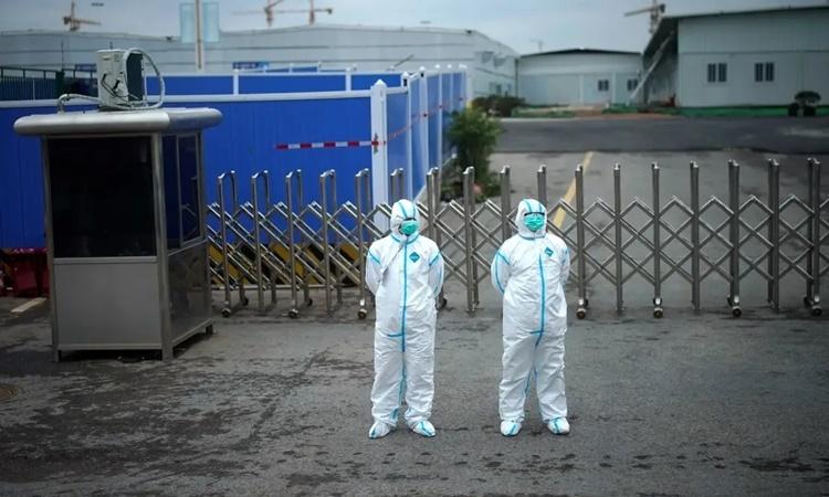 Nhân viên y tế mặc đồ bảo hộ đứng bên ngoài bệnh viện dã chiến Lôi Thần Sơn ở Vũ Hán, Trung Quốc, ngày 11/4. Ảnh: Reuters.