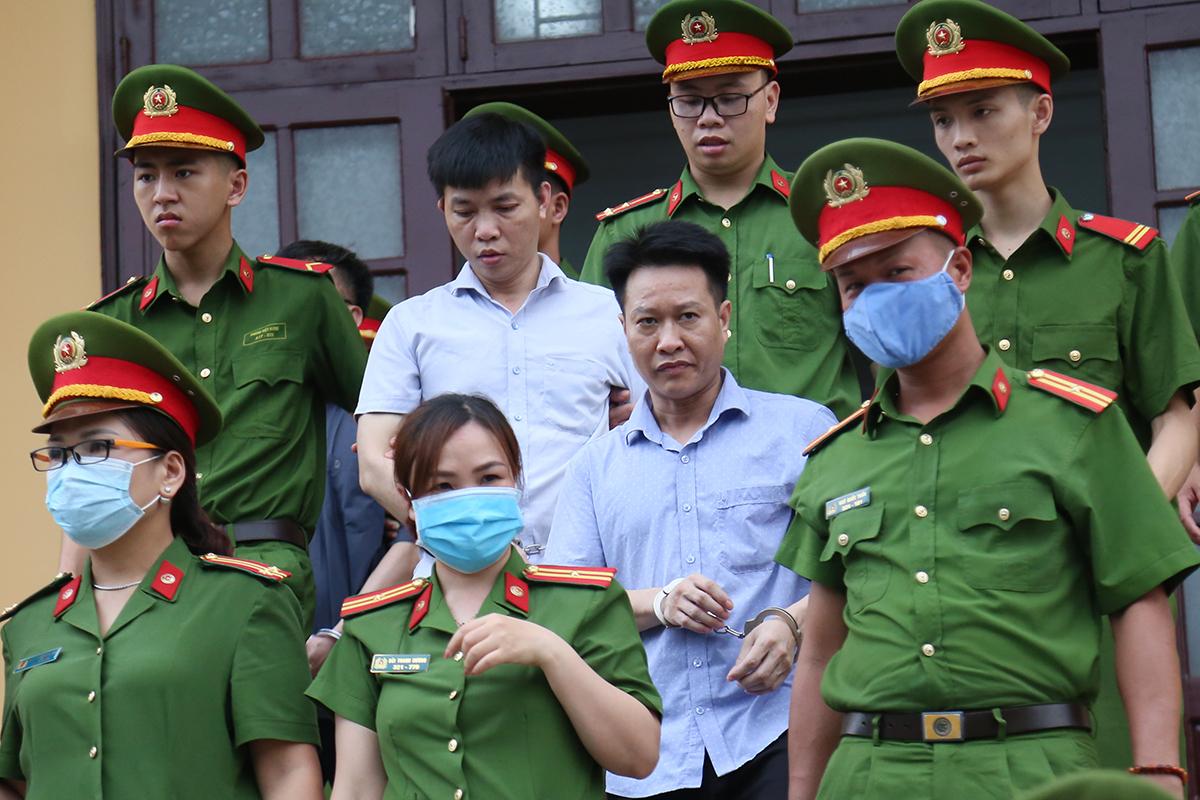 Cảnh sát dẫn giải Mạnh Tuấn và Khắc Tuấn rời phiên toà. Ảnh: Phạm Dự.
