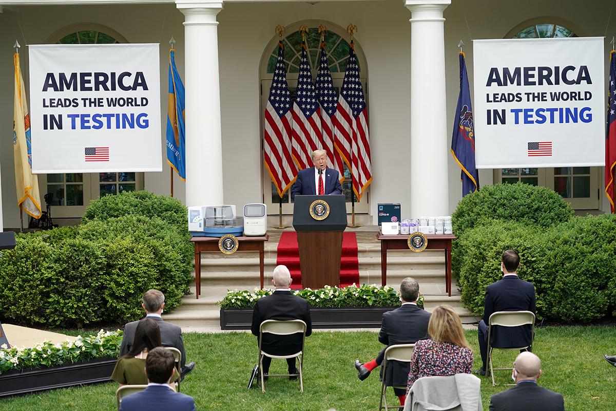 Tổng thống Trump phát biểu tại cuộc họp báo ở Nhà Trắng hôm 11/5, đằng sau là hai tấm bảng ghi Mỹ dẫn đầu thế giới về xét nghiệm. Ảnh: Reuters