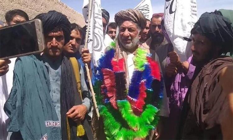 Cựu đại tướng Abdul Jalil Bakhtawar (chính giữa, đeo vòng cổ nhiều màu) cùng các tay súng Taliban ở phía tây tỉnh Farrah, ngày 10/5. Ảnh: NYT.