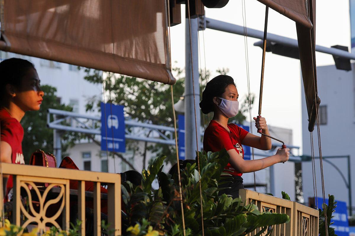 17h30, nhân viên một quán cà phê mặt tiền hướng Đông trên đường Nguyễn Văn Linh phải kéo tấm che vì nắng hoàng hôn phản quang từ toà nhà SHB. Ảnh: Nguyễn Đông.