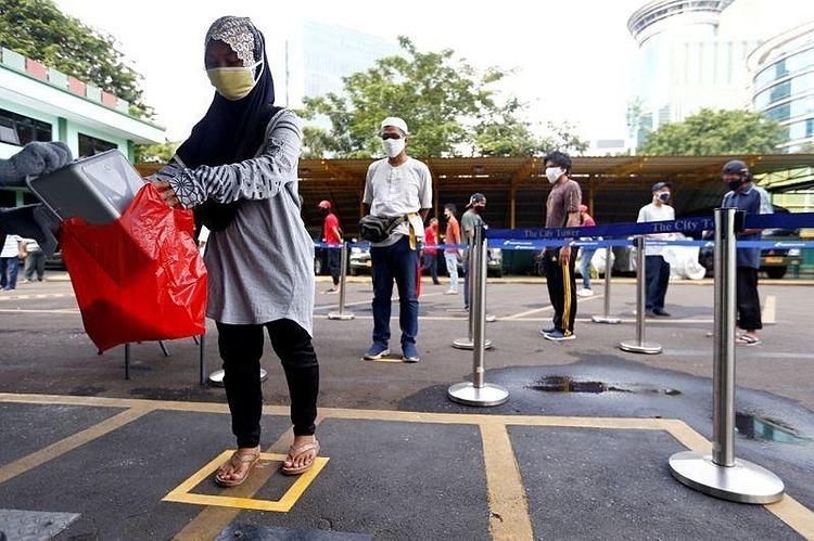 Người dân Indonesia đeo khẩu trang xếp hàng chờ lĩnh gạo trợ cấp ở Jakarta hôm 4/5. Ảnh: Reuters.