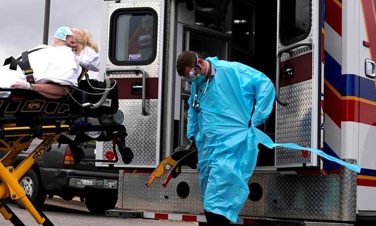 Nhân viên y tế trong trang phục bảo hộ chuẩn bị đưa bệnh nhân Covid-19 lên xe cứu thương ởOklahoma, Mỹ tháng trước. Ảnh: Reuters.