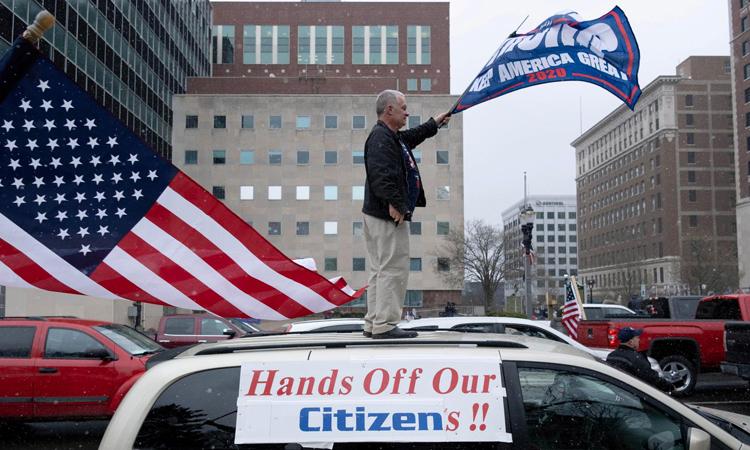 Người dân biểu tình chống quyết định kéo dài lệnh phong tỏa để ngăn Covid-19 tại thành phốLansing, bang Michigan, Mỹ, hôm 15/4. Ảnh: Reuters.