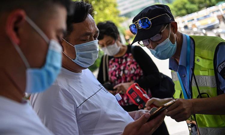 Một nhân viên kiểm tra thân nhiệt và mã y tế trên điện thoại của hành khách tại nhà ga xe lửa Hán Khẩu, Vũ Hán hôm nay. Ảnh: AFP.