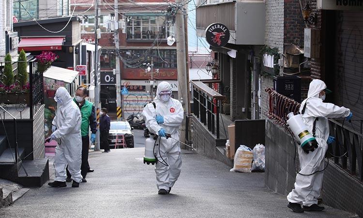 Các nhân viên vệ sinh khử trùng đường phố và các địa điểm công cộng tại khu Itaewon ở Seoul, Hàn Quốc hôm 12/5. Ảnh: Reuters.