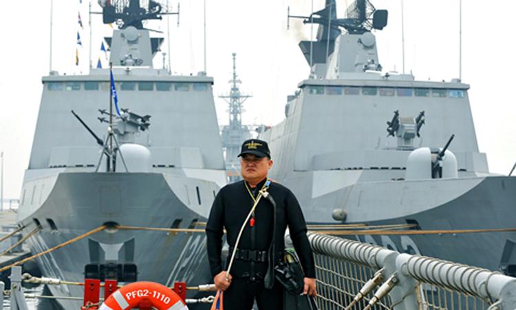 Một người ếch đứng trước hai tàu khu trục lớpLafayette ở thành phố Cao Hùng, Đài Loan hồi tháng 1. Ảnh: Taipei Times.