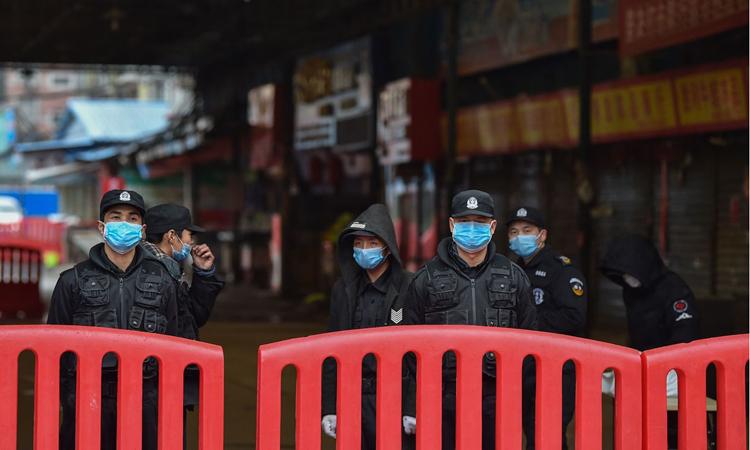 Cảnh sát và nhân viên an ninh dựng rào chắn bên ngoài chợ Hoa Nam, Vũ Hán, hôm 24/1. Ảnh: AFP.