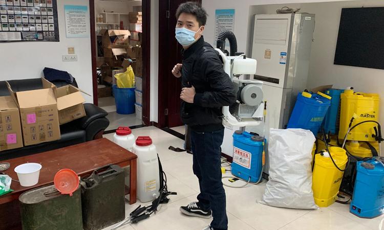Lư Tuấn Khanh thử thiết bị khử trùng tại công tyKhương Duy ở Vũ Hán. Ảnh: WSJ.