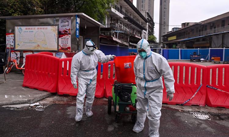 Nhân viên khử trùng tại chợ Hoa Nam, Vũ Hán, hôm 30/3. Ảnh: AFP.