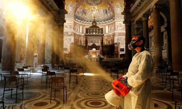Người đàn ông khử trùng bên trong nhà thờ Trastevere Basilica ở Rome, Italy, ngày 11/5. Ảnh: Reuters.