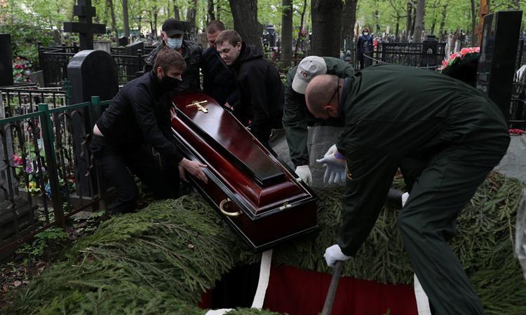 Nhân viên tang lễ chôn cất người chết vì Covid-19 ở Moskva , ngày 9/5. Ảnh: Reuters.