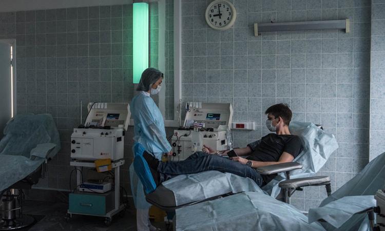 Người đàn ông hiến máu sau khi bình phục vì nhiễm nCoV để giúp nghiên cứu về kháng thể tại bệnh viện ở Moskva. Ảnh: NYTimes.