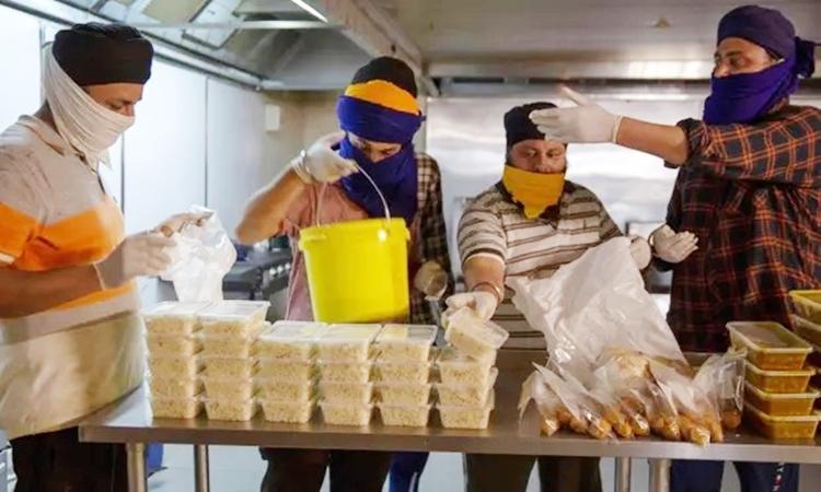 Tình nguyện viên trong một đền thờ của người Sikh ở Melbourne chuẩn phị phân phát thực phẩm. Ảnh: AFP.