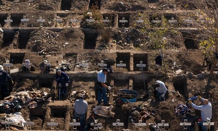 Nhân viên nghĩa trang ở thủ đô Santiago, Chile, đào sẵn những ngôi mộ mới hôm 14/5. Ảnh: AFP.