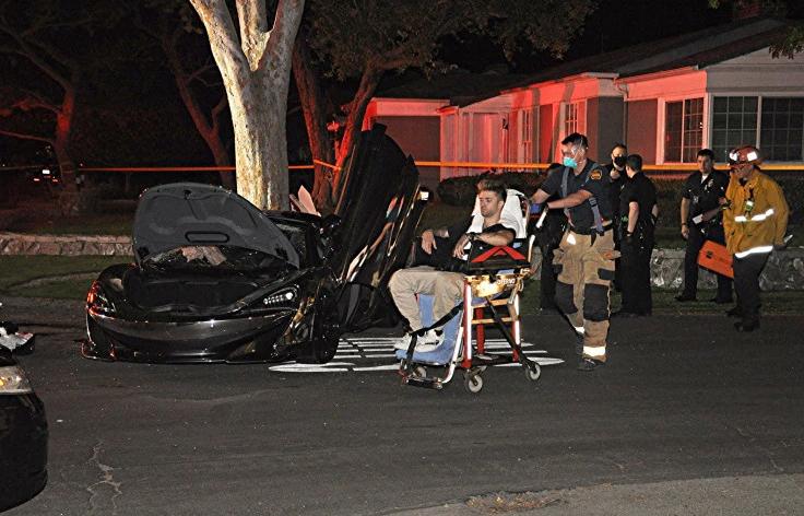 Chiếc McLaren nằm cạnh một cây lớn, nắp cốp mở toang. Bên cạnh là tài xế của siêu xe, ngồi trên xe đẩy. Ảnh: