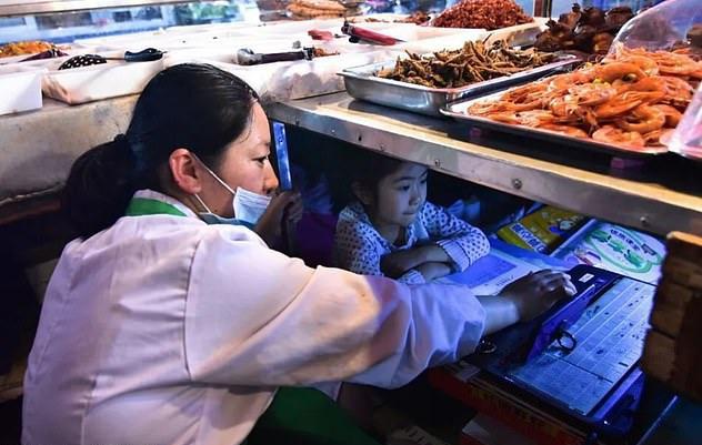 Khi vắng khách, Zhao Weiwei, mẹ của Enya giúp con làm bài tập. Ảnh: Meilliwufeng/ WeChat.