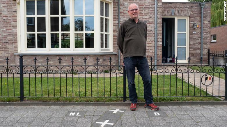 ÔngJulien Leemans, đứng trước ngôi nhà có đường biên giới Bỉ - Hà Lan chạy thẳng qua. Phần chữ B thuộc Bỉ, chữ NL thuộc Hà Lan. Ảnh: CNN