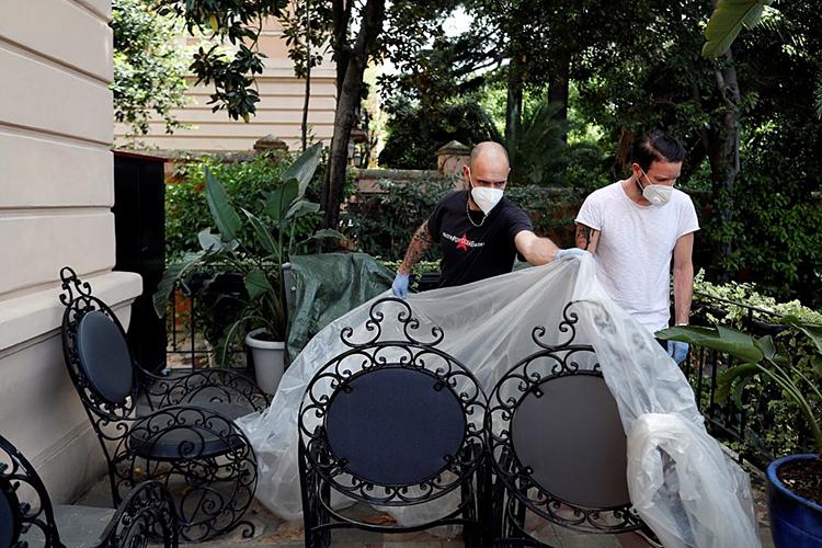 Nhân viên một nhà hàng ở Rome hôm 15/5 chuẩn bị mở lại nhà hàng vào tuần tới. Ảnh: Reuters.