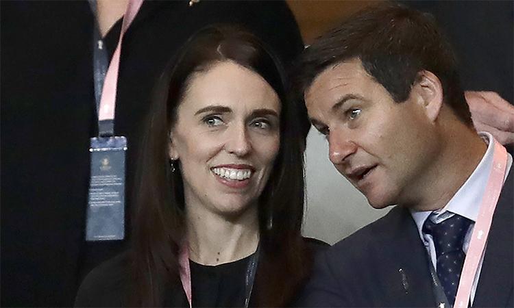 Thủ tướng New Zealand Jacinda Ardern (bên trái) cùng chồng, Clarke Gayford (bên phải), xem một trận bóng bầu dục, năm 2019. Ảnh: AP.