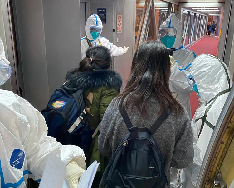 Amy và hành khách cùng chuyến bay được đo thân nhiệt khi xuống máy bay ở Bắc Kinh hồi cuối tháng 2. Ảnh: NYT.