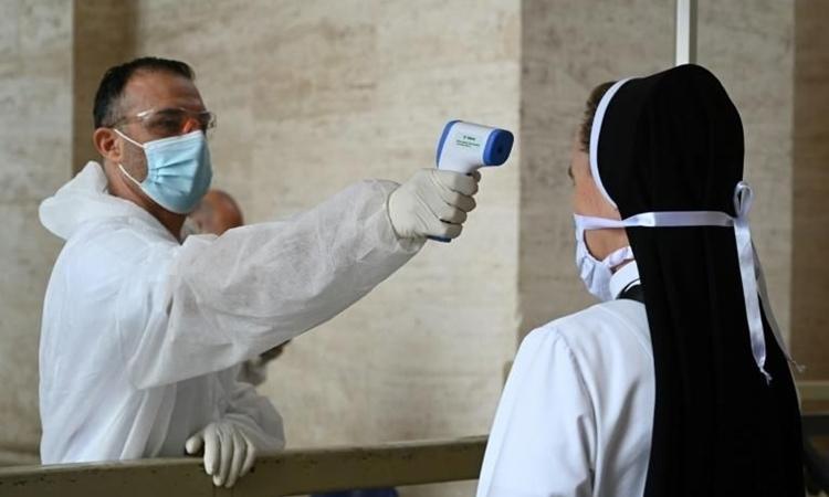 Nhân viên y tế đo thân nhiệt cho một nữ tư trước khi vào nhà thờ Thánh Peter hôm 18/5. Ảnh: AFP.
