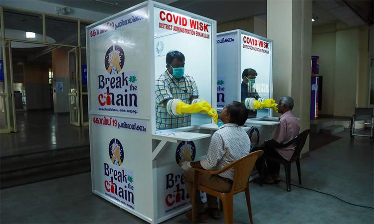 Nhân viên y tế lấy mẫu tại quầy xét nghiệm nCoV ở đại học y Ernakulam, bang Kerala, Ấn Độ, ngày 20/4. Ảnh: AFP.