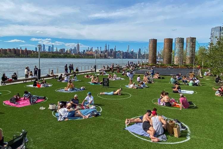 Người dân tắm nắng thành từng nhóm trong vòng tròn kẻ sẵn ở công viên Domino, Brooklyn, New York, hôm 16/5. Ảnh: Reuters